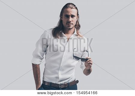 Confident in his perfect style. Handsome young man in white shirt looking at camera while standing against grey background