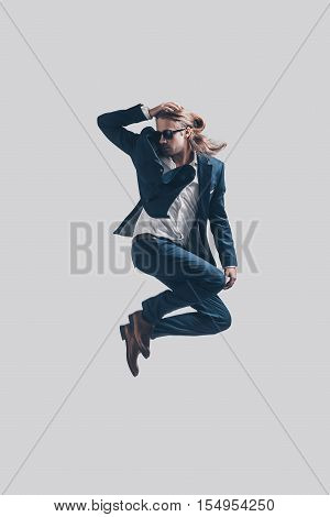Feeling confident in his perfect style. Handsome young man in full suit jumping against grey background