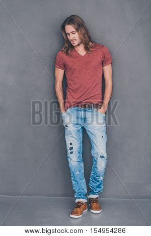 Casually handsome. Full length of handsome young man in casual wear holding hands in pockets and looking thoughtful while standing against grey background