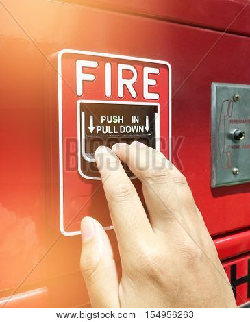 Soft Focus Of A Hand Reaching And Pulling A Red Fire Alarm Switch. Red Fire Alarm. Push In Pull Down