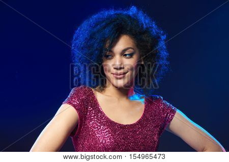 Closeup of smiling mixed race woman in sequined dress on a party over blue background with backlit