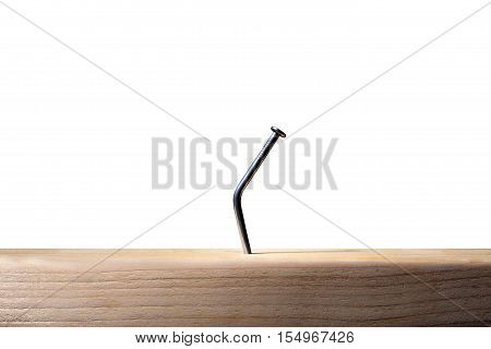 Still Life of a Bent Construction Nail in Wood on White Background