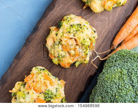 Baked vegetable patties with carrots, broccoli and cheese on dark wooden serving board. Top view