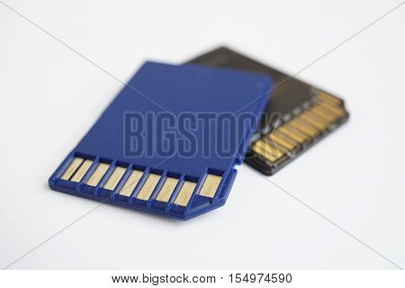 Two isolated plastic blue and black compact memory card (SD card - Secure Digital card) used in cameras, computers and video cameras in a blue color with metal connectors in the golden color