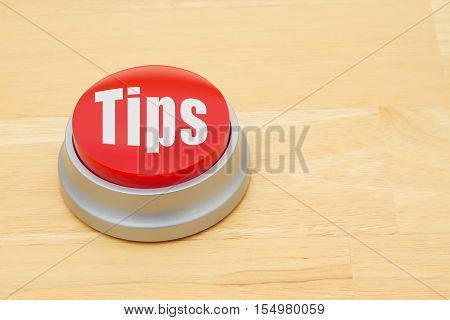 A tips red push button A red and silver push button on a wooden desk with text Tips