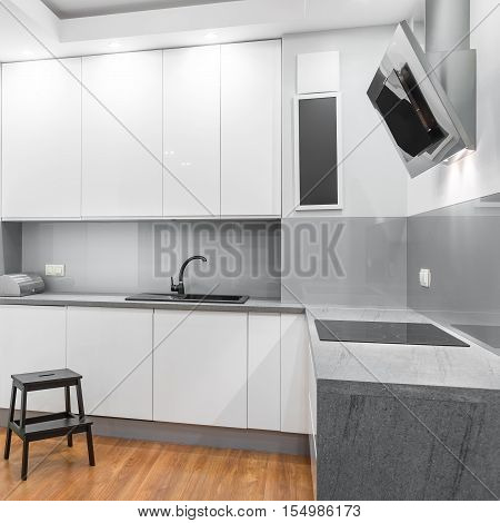 White high-gloss kitchen with wooden step stool and exhaust hood