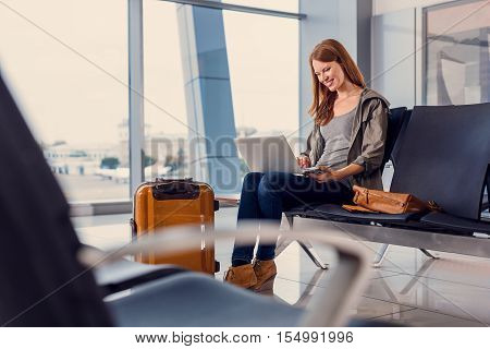 Chatting with friends before departure. Close up photo of smiling young woman holding laptop and working on it during waiting for departure at airport