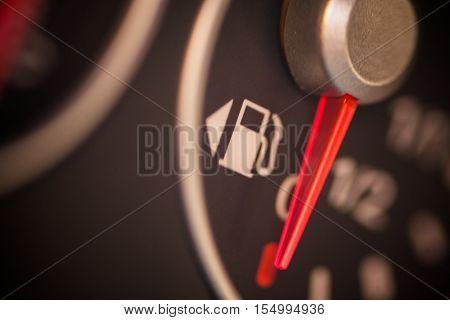 Color close up image of a car's fuel gauge.