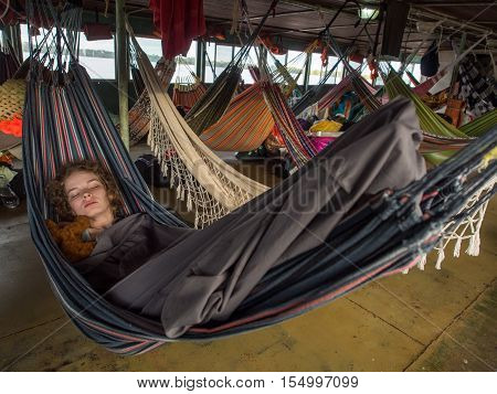 Young woman is resting on hammocks on a deck of the cargo boat.
