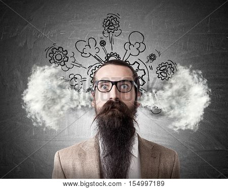 Portrait of baffled man with long beard and steam going out of his head. Sketch with cogs is drawn on the blackboard behind him. Concept of frustration
