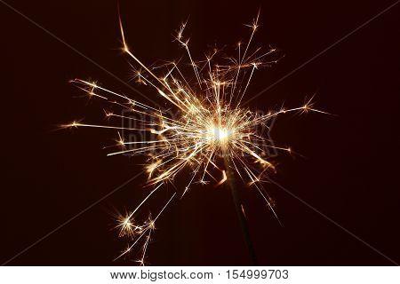 Bright sparkler lit against a dark background.