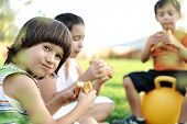 pic of children playing  - Three children in nature playing and eating together - JPG
