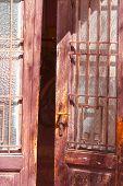 Постер, плакат: старые деревянные двери наполовину открытые