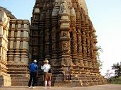 picture of deo  - A guide showing the tourist details by shining a mirror on Dulhadeo temple at Khajuraho India - JPG