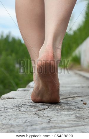 A young woman goes barefoot