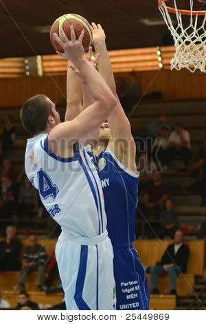 KAPOSVAR, HUNGARY - OCTOBER 15: Jozsef Lekli (in white) in action at a Hugarian National Championship basketball game Kaposvar (white) vs. Jaszbereny (blue) on October 15, 2011 in Kaposvar, Hungary.