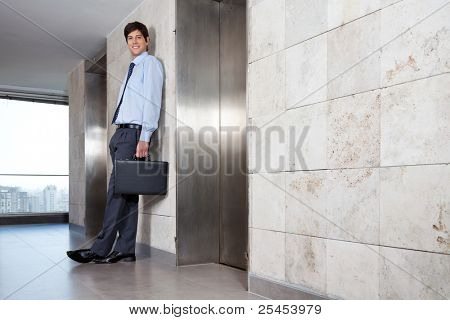 Low angle view of handsome corporate manager standing near lift
