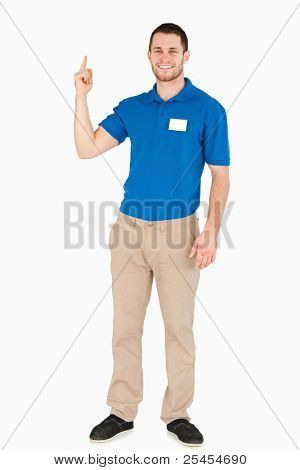 Smiling young salesman pointing upwards against a white background