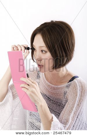 Bautiful asian woman applying mascara