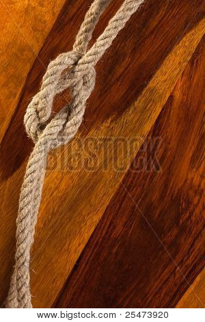 Rope knot on a teak wood background
