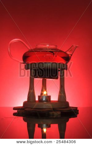 Teapot with fresh black tea on red