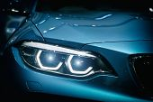 Car Headlight And Hood Of Powerful Sports Blue Car With Blue Glare On Dark Background. Close Up At C poster