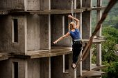 Back View Of A Young Brave Woman Walking On A Slackline Against The Background Of High Empty Buildin poster