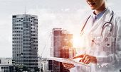 Double Exposure Of Young Woman Doctor In White Medical Suit Touching Tablet With Her Finger And City poster