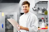 cooking, profession and people concept - happy smiling male chef cook writing to clipboard and doing poster