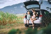 Mother And Children Sitting In An Open Car Trunk And Watching On Nature And Countryside. Family In R poster