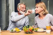 Senior Couple Enjoy Eating  Healthy Breakfast Together In The Kitchen.retirement Couple Concept poster