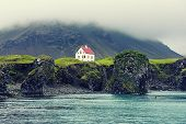 Lonely Icelandic House With Red Roof On The Sea Coast With Green Grass Meadow, Rocks Anf Foggy Sky.  poster