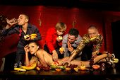 stock photo of bachelor party  - Four guys having fun with woman decorated  by fruits - JPG