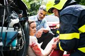 A Firefighter Helping A Young Injured Woman Sitting By The Car On A Road After An Accident. poster