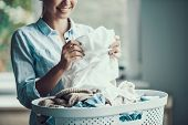 Young Beautiful Smiling Woman Holds Clean Clothes. Closeup Of Happy Beautiful Girl Holding Fresh Clo poster