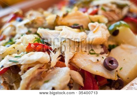 Cod fish cooked with peppers olives and herbs