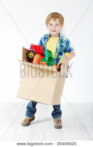 Niño con caja de cartón llena de juguetes. Movimiento y concepto de crecimiento