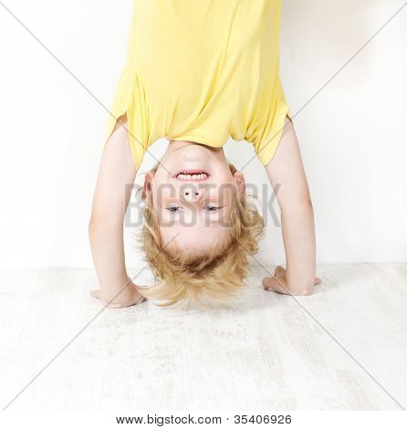 Funny Child Standing Head Over Heel. Close Up Portrait
