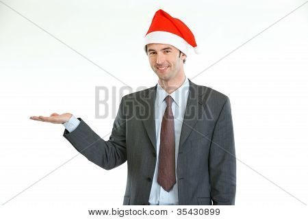 Smiling Businessman In Santa's Hat Presenting Something On Empty