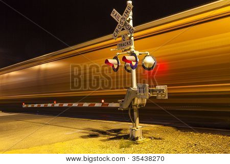 railroad crossing with passing train by night