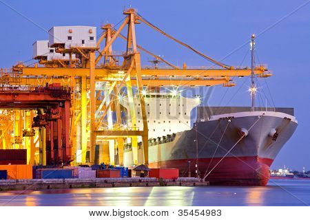 Industrial Container Cargo freight ship with working crane bridge in shipyard at dusk for Logistic Import Export background