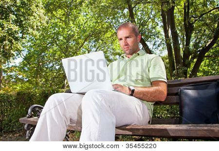 Businessman working with a laptop while sitting on a bench in park
