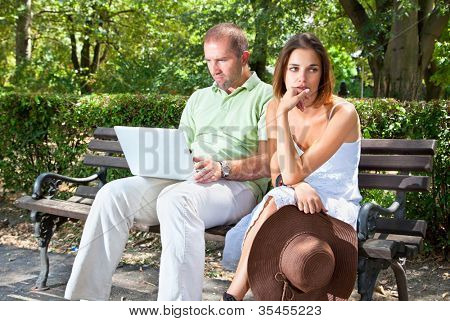 Upset young female looking away while her husband using laptop on bench in parke