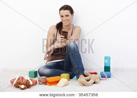 lächelnde Mutter auf Fußboden Kaffeetrinken umgeben von Babyspielzeug.