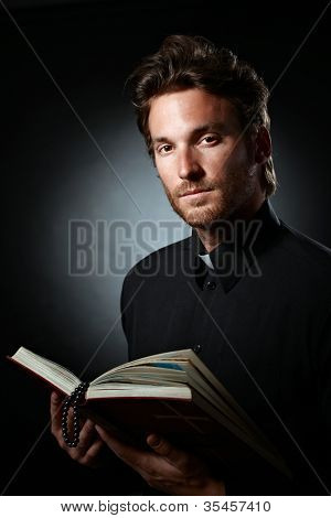 Portrait of young cleric holding holy Bible, looking at camera.