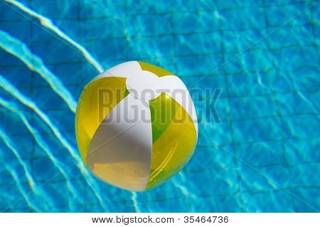 Inflatable yellow beachball floating at the water