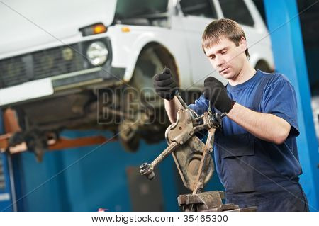 automotive mechanic worker tighten screw with spanner during automobile car maintenance at lever repair service station