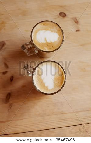 coffee latte in two tall glasses on wood, shallow dof