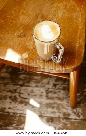 coffee latte on  woden chair and sunbeam