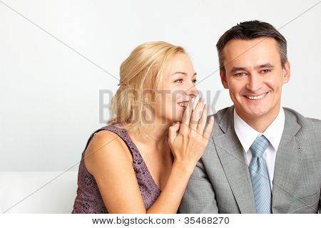 Cheerful woman whispering something funny in her husband�s ear